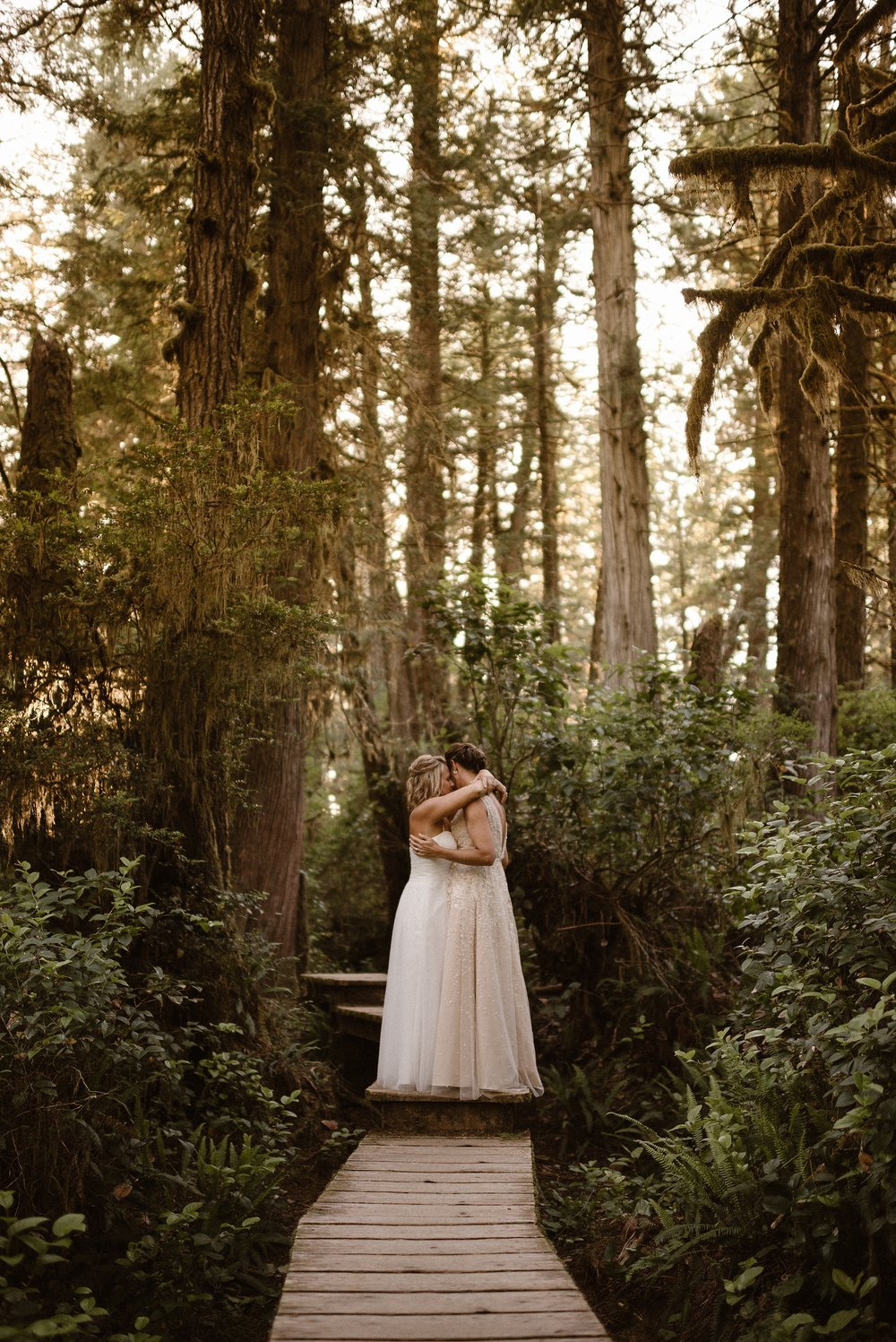 Two brides, both in long wedding dresses, embrace on a wooded walkway with dark, old-growth trees towering around them. Thick, lush foliage, a common feature of the PNW, surrounds the couple in this photo captured by Pacific Northwest photographer Adventure Instead.