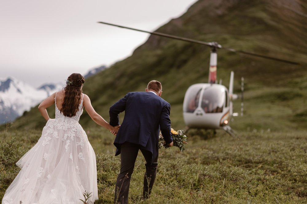The helicopter lands in the distance and Jordyn and Connor take hands to hike toward it to their next adventure. The bride and groom will leave this first location featuring green mountainside and glacial-peaks where they had their elopement ceremony and head to the next spot in their Alaska helicopter elopement story.
