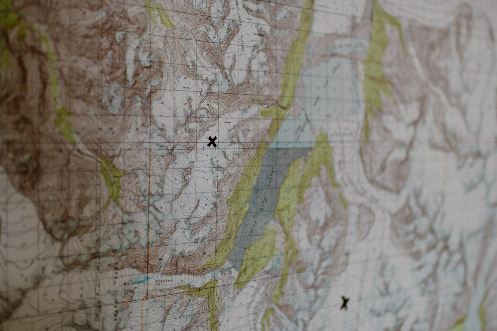 A map of Alaska hangs on the wall with several Xs marked as destinations for Jordan and Connor's Alaska Helicopter elopement story. This photo, taken by Alaska elopmenet photographer Adventure Instead, shows the general plans and destination for the couples helicopter elopement.