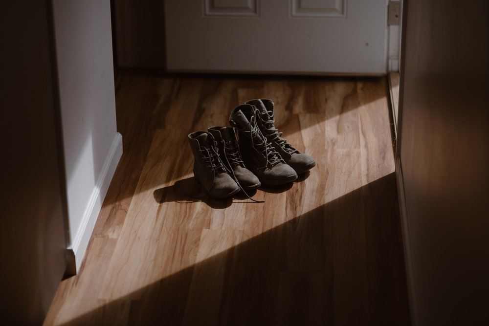Two sets of hiking boots sit upright on a wooded floor in an Alaskan Airbnb. These boots will be put on and used by both the bride and groom in their alaska destination wedding.