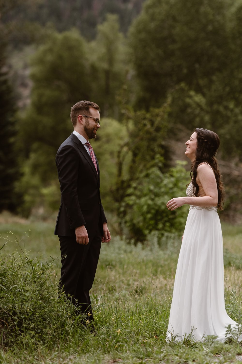 The bride and groom, Katie and Logan, stare at each other in the moments following their first look. As they stand in a green field and look at each other before their adventure elopement, Logan looks at Katie in awe as Katie smiles and laughs at him.