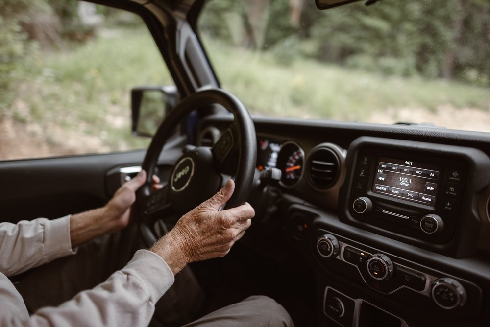 A driver holds his hands firmly on the steering wheel of the Jeep wedding car as he shows Katie and Logan what off road driving is all about as part of their adventure elopement. The Jeep will adventure all around Ouray for their Colorado mountain wedding, which was captured by adventure wedding photographer, Adventure Instead.