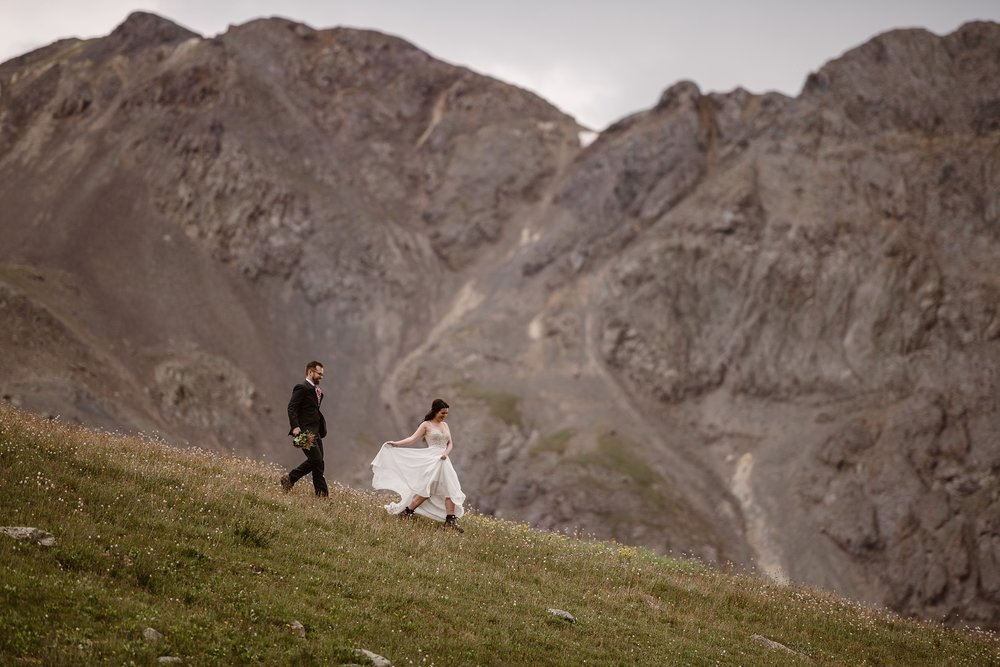 The bride runs down the side of a a green mountain meadow, holding up her dress so it trails behind her. Her groom, following close behind, holds a backpack and a bouquet of flowers. Behind them, a giant granite part of the mountain is looming. This was one of the best elopement ideas the two had as a part of their adventure elopement.