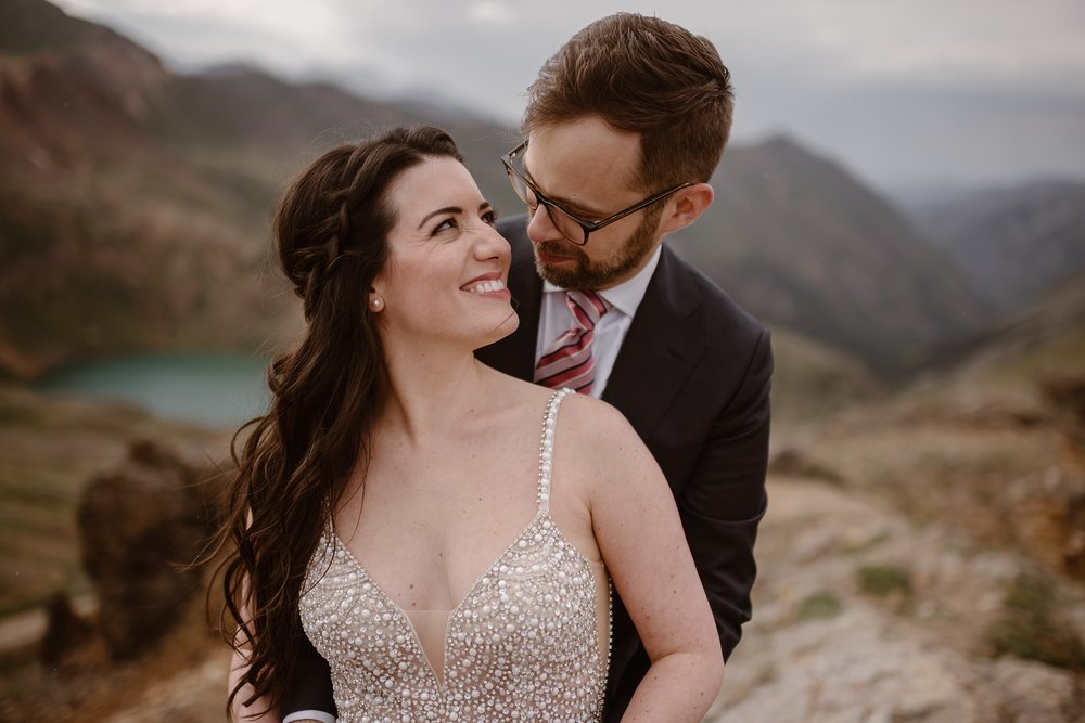 Logan, the groom, holds his bride, Katie by wrapping his arms around her. Katie, shown from the bodice of her pearl wedding dress up, looks back at Logan, smiling and staring into his eyes. The two stand at the forefront of the image, but in the background, a striking, turquoise alpine lake can be seen in the distance at the bottom of the basin.