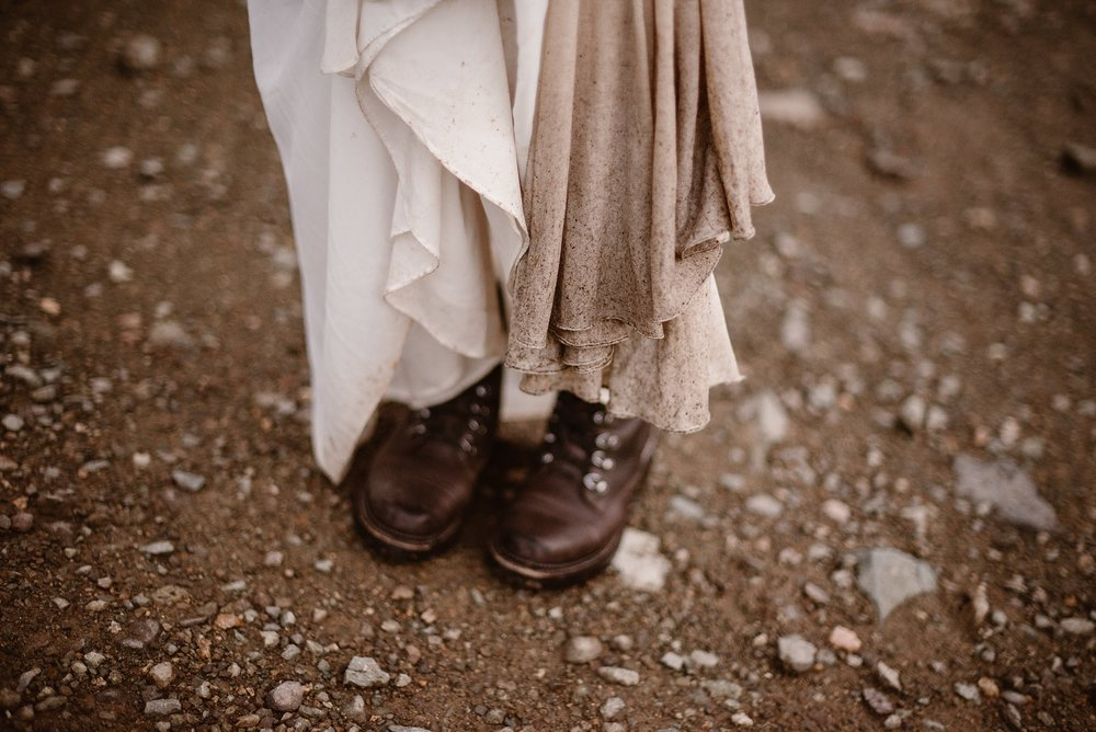 Katie, the bride, shows off how dirty the bottom of her wedding dress got on the hike up to their elopement ceremony spot by hiking up the wedding dress skirt to show her hiking boots. The bride and groom had to battle a sudden storm during their day, but their Colorado mountain wedding, but their unique eloping idea was still a success.