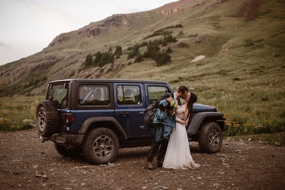 Katie and Logan, the bride and groom, stop for a moment and kiss in front of their navy blue adventure Jeep. Katie and Logan, a bit muddy and dirty from their hike up and down the mountain to and from their elopement spot, chose this location so they could have a Jeep wedding car that would off road drive them to their ideal elopement spot.