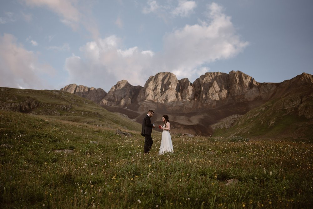 Katie and Logan, the bride and the groom, stand in a meadow at the base of a Ouray, Colorado mountain as they read their vows and pledge their lives to each other. This part of their elopement ceremony was one of their small wedding ideas they wanted to implement in their destination elopement.