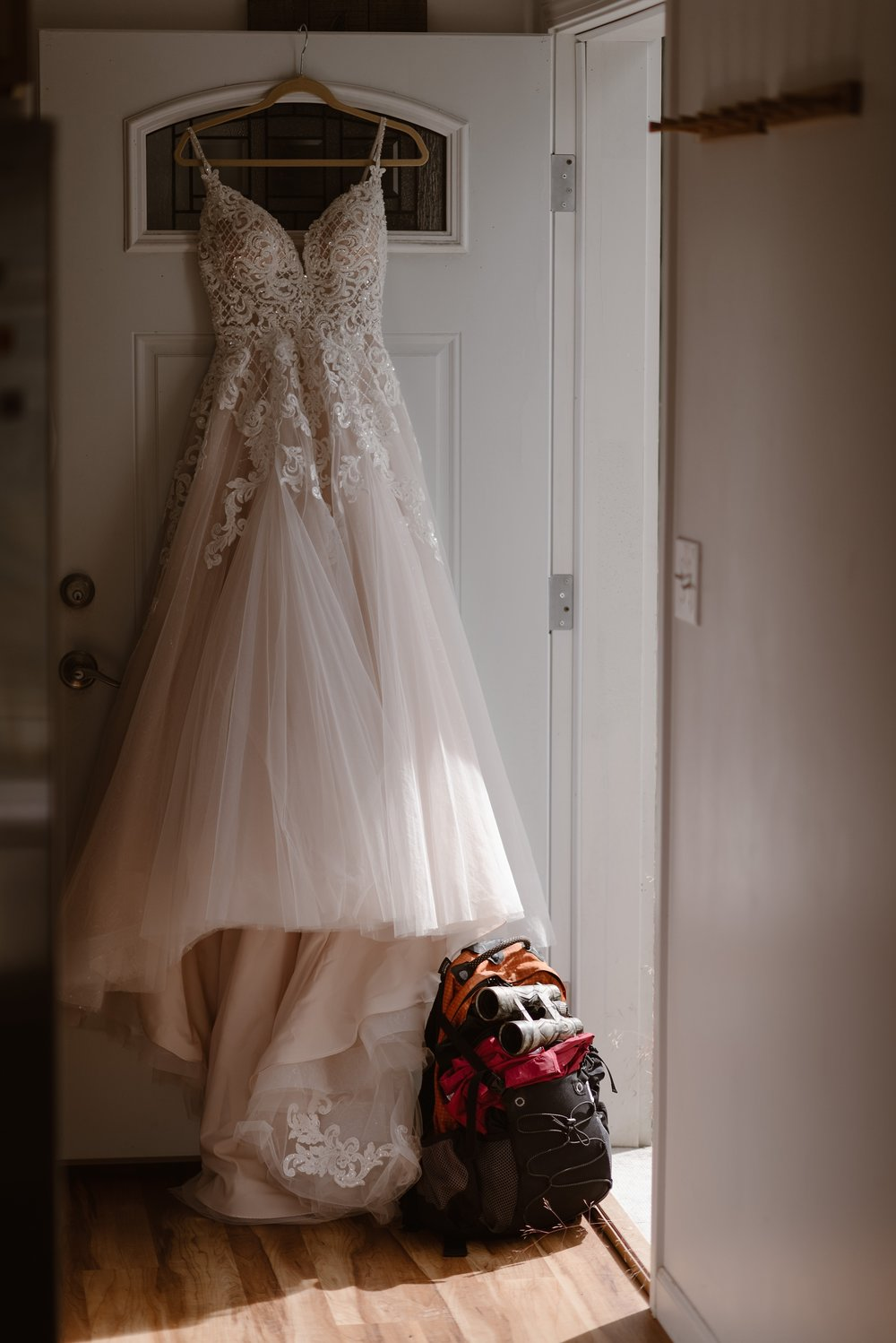 The white, champagne, and lace wedding dress hangs from the door of the front of the Airbnb before this couple's Alaska's helicopter elopement story begins. Beneath the skirt is a backpack and a pair of dirt-covered binoculars.