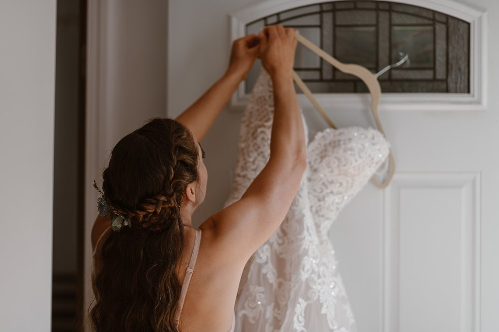 The bride reaches up to take down the wedding dress hanging from the door before her alaska elopement begins. This photo was captured by elopement wedding photographer Adventure Instead.