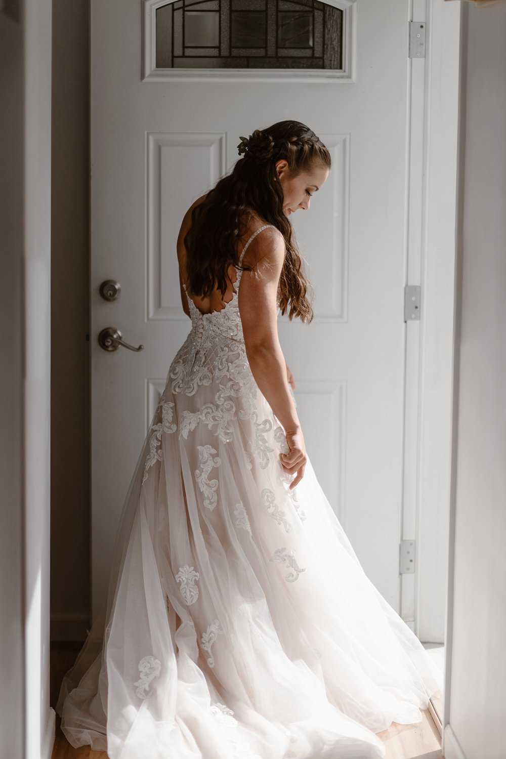 This image is a full-length view of the bride in her wedding dress before her Alaska destination wedding. The bride looks down toward the bottom of her white and champagne-colored wedding dress in this elopement photo taken by Adventure Instead, an elopement photographer.