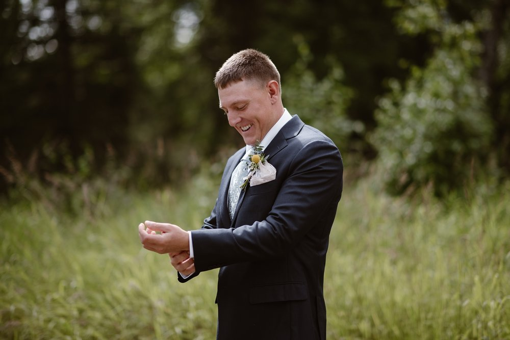 In the lush, green yard of the Alaskan Airbnb, the groom adjusts his cuff-links and long-sleeve shirt. This image, captured by Alaska elopement photographers Adventure Instead, shows a smiling groom moments before his Alaska destination wedding.