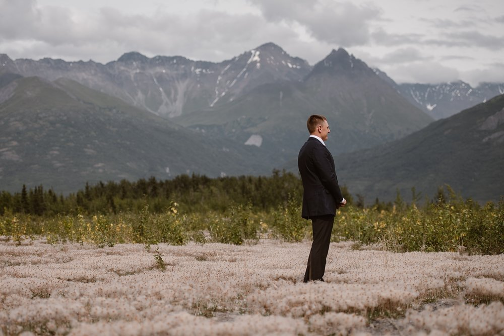 The groom, wearing his suit, looks off into the distance as he stands in a flowered field with dramatic mountain peaks in the background before his Alaska destination wedding. This elopement photo was taken by Adventure Instead, an elopement wedding photographer.