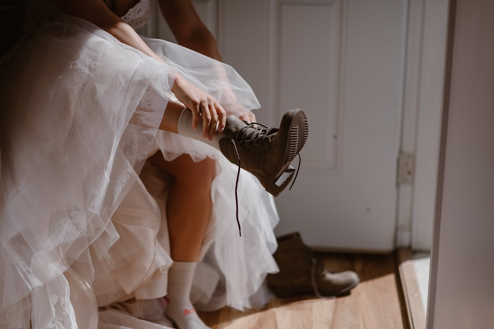 In this elopement photo captured by elopement photographer Adventure Instead, the bride pulls on her hiking boots under the ruffles and lace of her wedding dress before the start of her destination elopement. Beneath her dress, white and pink socks peek out.