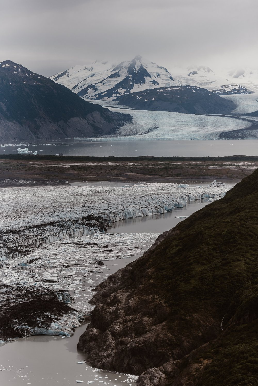 This image shows so much of the Alaska landscape — glaciated mountain peaks, a glacial lake, and snowy mountains the distance. These elopement photos were captured by elopement photographer Adventure Instead during Jordyn and Connor's Alaska Elopement Story.
