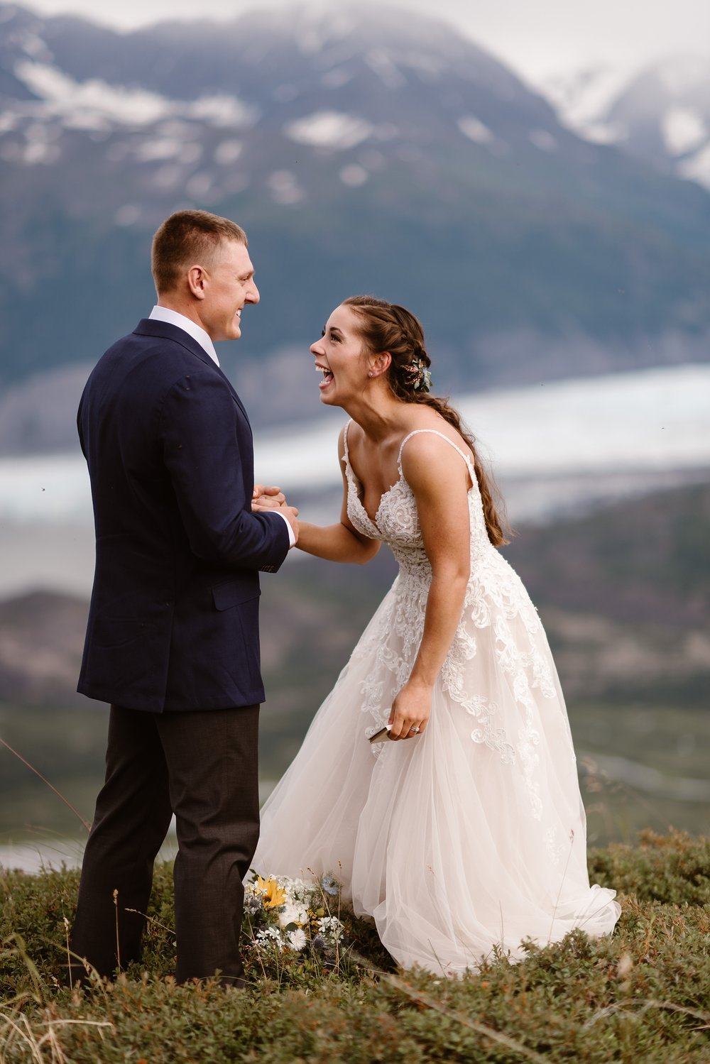 Jordyn and Connor, the bride and groom, hold hands during their elopement ceremony at the top of a green, lush hill with mountains in the background. Jordyn leans in, laughing at her groom, and Connor smiles at Jordyn in this elopement photo captured by Adventure Instead, an elopement wedding photographer.