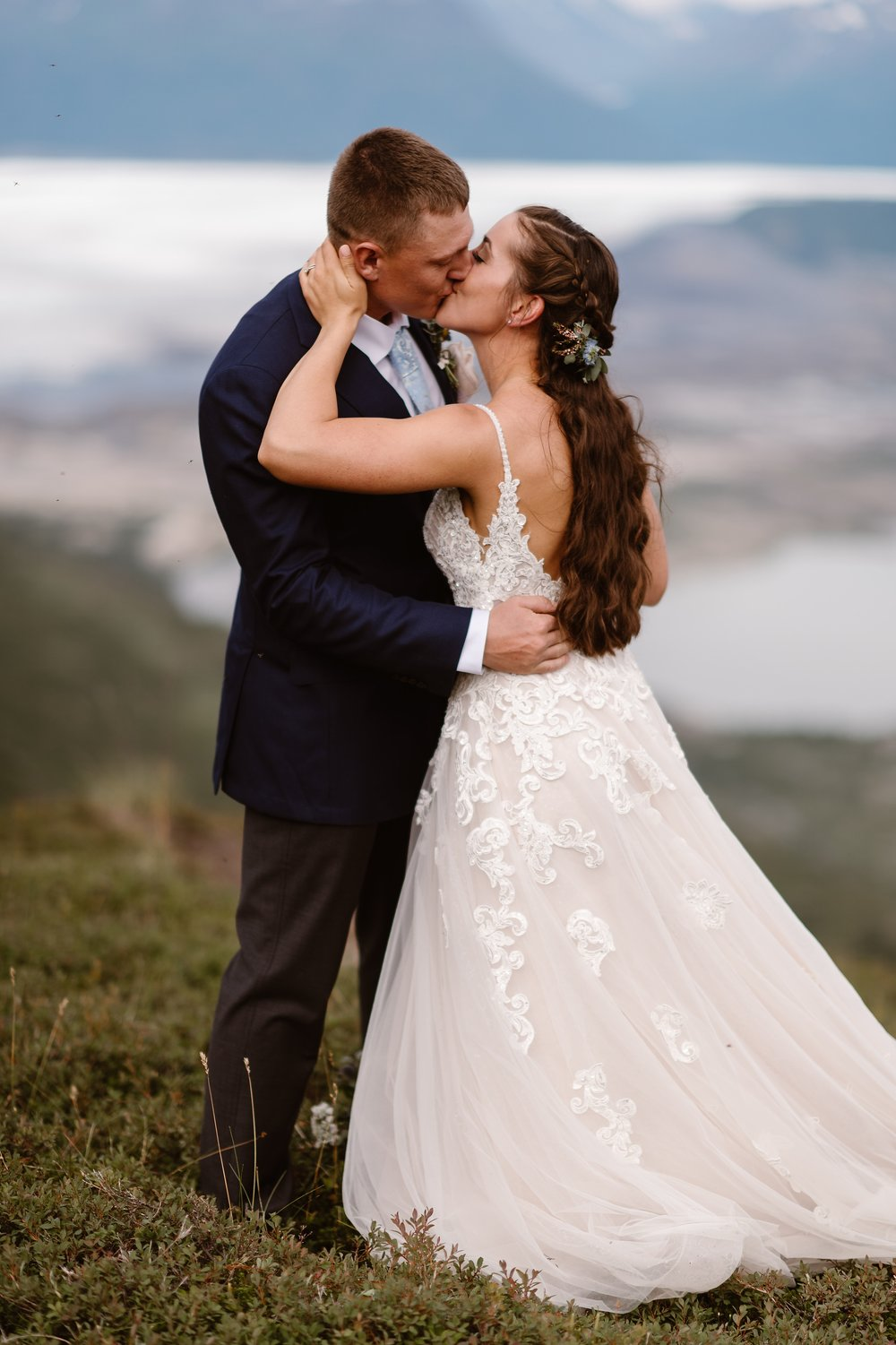 The bride and groom embrace and kiss during their elopement ceremony. These elopement photos, captured by Adventure Instead, Alaska wedding photographers, show Jordyn and Connor during their Alaska Helicopter Elopement Story.