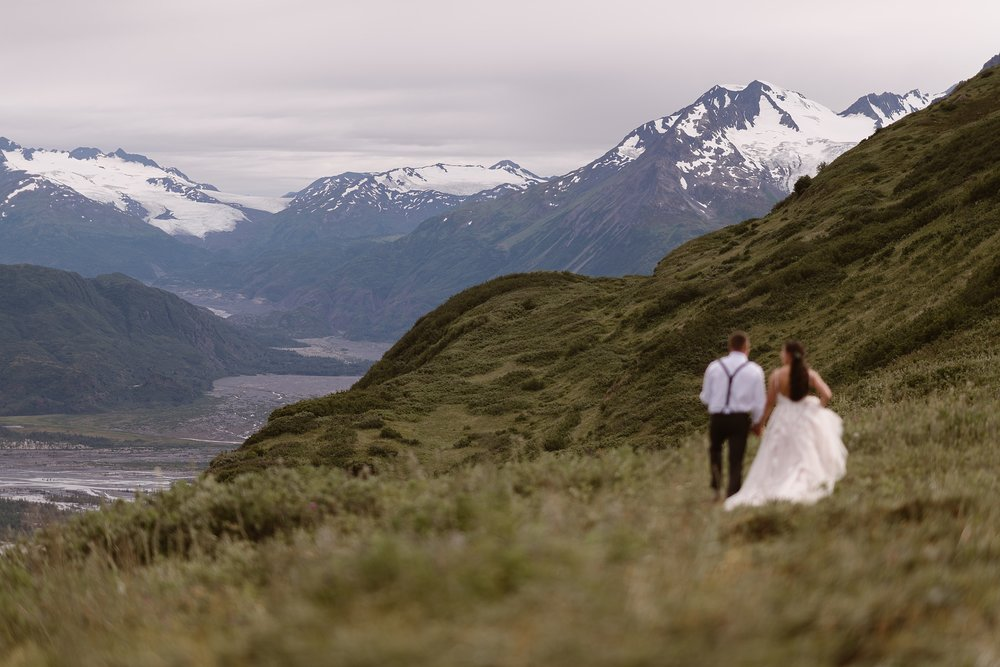 The bride and room stand to the right of the image in a green, lush field with their backs to the camera. They're staring into the distance at gorgeous, snowy mountain peaks and a glacial lake in these elopement pictures captured by elopement photographer Adventure Instead.