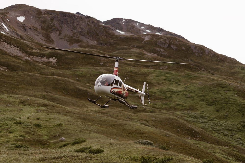 The helicopter that's been flying Jordyn and Connor to their elopement locations flies into view. In the background of this image is a gorgeous, green, Alaska mountainside with granite peaks at the top.