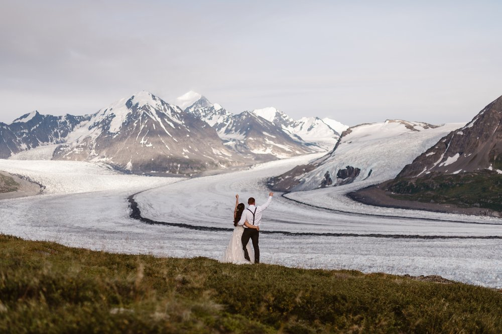 The bride and groom, Jordyn and Connor, stand facing away from the camera in this elopement photo captured by Adventure Instead, an elopement photographer. The two have arms wrapped around each other's waists while they each raise a triumphant hand in the air as they look into the distance at snowy mountain peaks and glaciers.