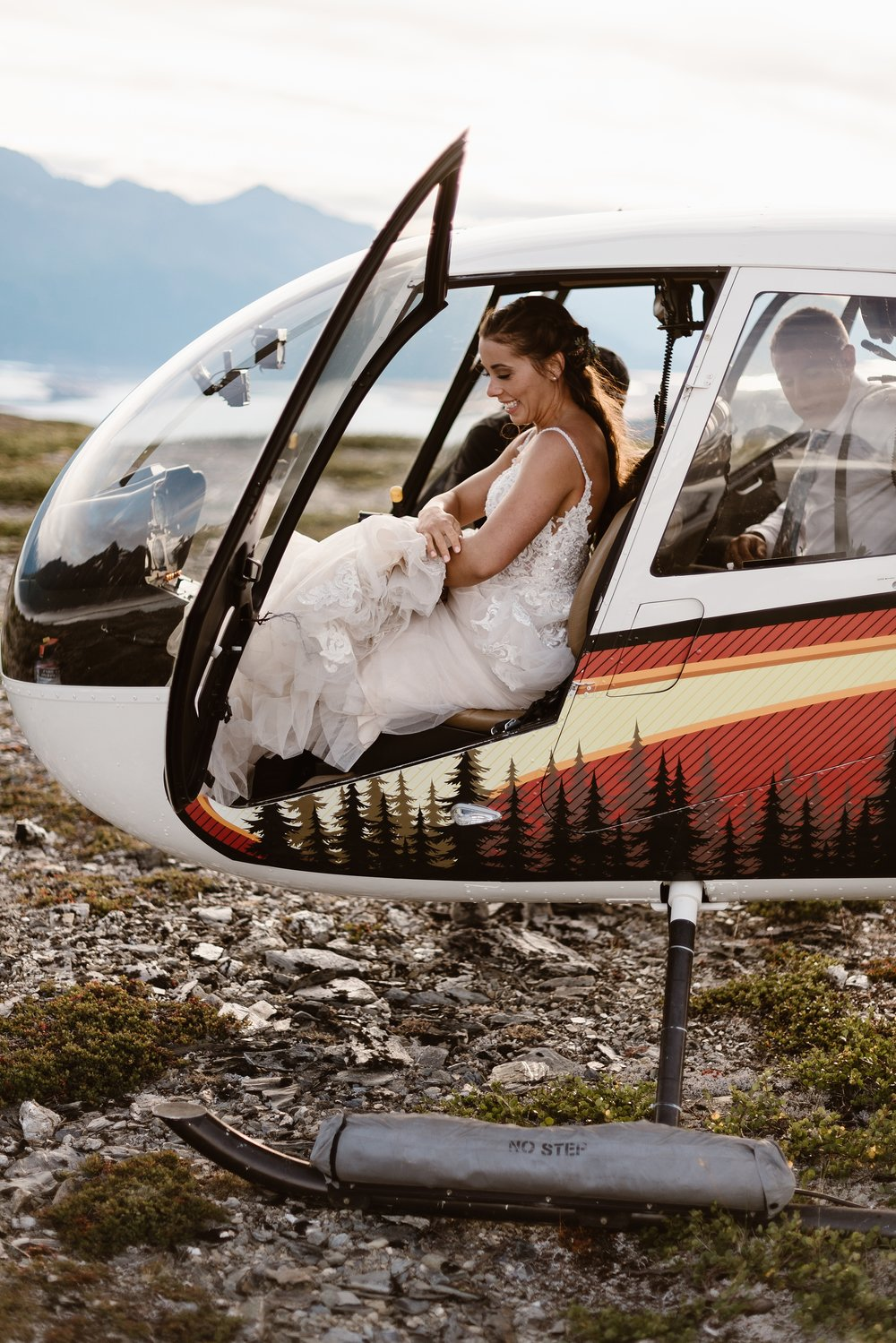 The bride, Jordyn, bundles up her wedding dress as she tries to fit the entirety into the front seat of the helicopter. This unique eloping idea was captured by Alaska wedding photographers Adventure Instead.