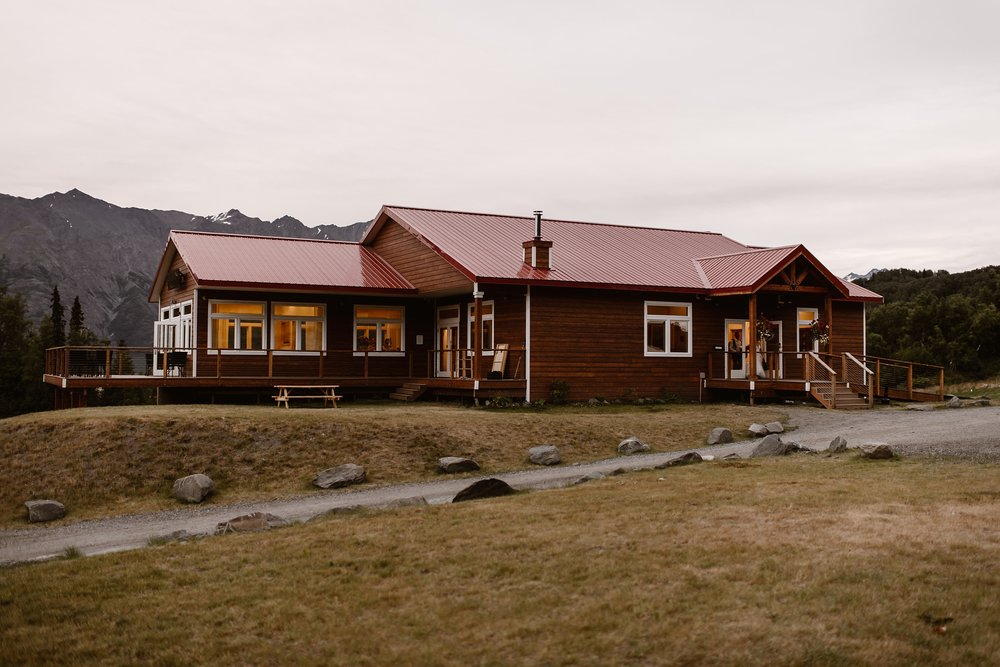 After the bride and groom's epic destination elopement, the helicopter flew them back to the Knik River Lodge, featured in this photo captured by elopement photographer Adventure Instead. The lodge is rustic and built of deep-red logs and equipped with a red roof. In the background, the tops of mountains peak through.
