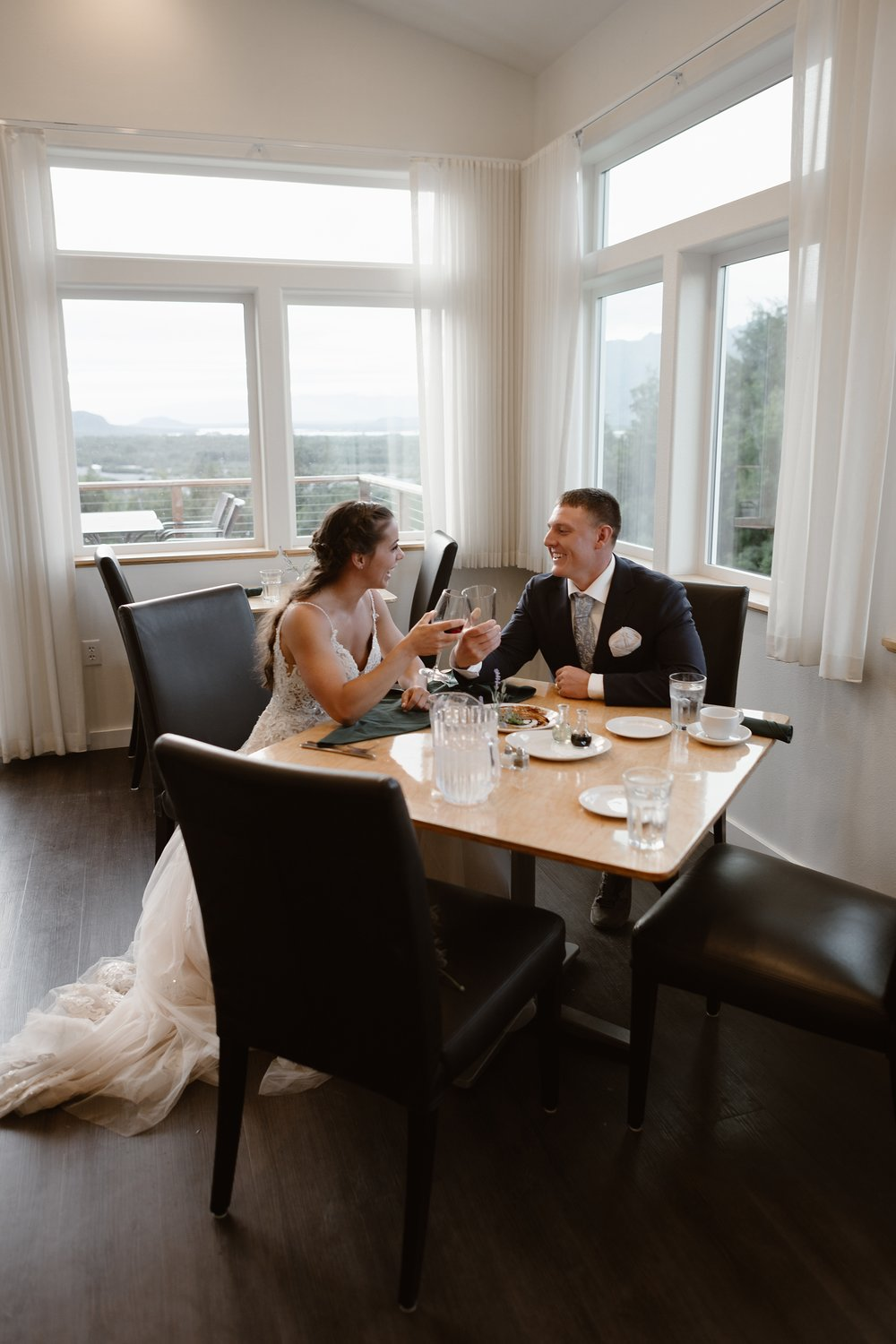 The Knik River Lodge stayed open past their closing time so they could cook the bride and groom a romantic post-elopement meal. This is just one of the unique eloping ideas that could be included in a reception after eloping. In this photo, Jordyn and Connor sit at a wooden table made for four and toast empty glasses over a plate of delicious-looking food.