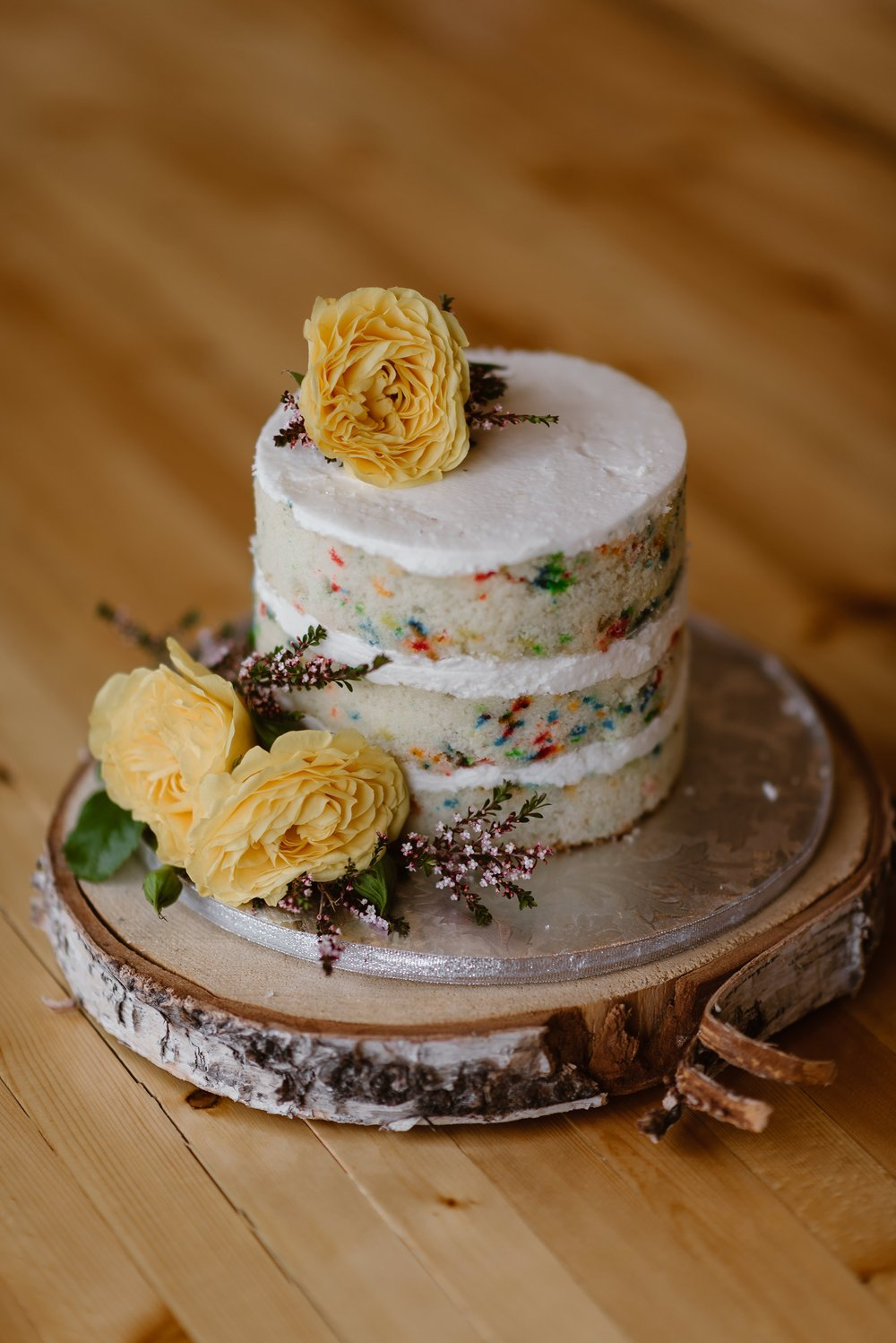 It was Connor's (the groom's) birthday on their elopement day, so Jordyn (the bride) surprised Connor with a confetti wedding cake. In this elopement photo captured by Alaska wedding photographer Adventure Instead, a tiny, frosted confetti cake sits on a sliver of cut wood. Yellow flowers adorn the cake.