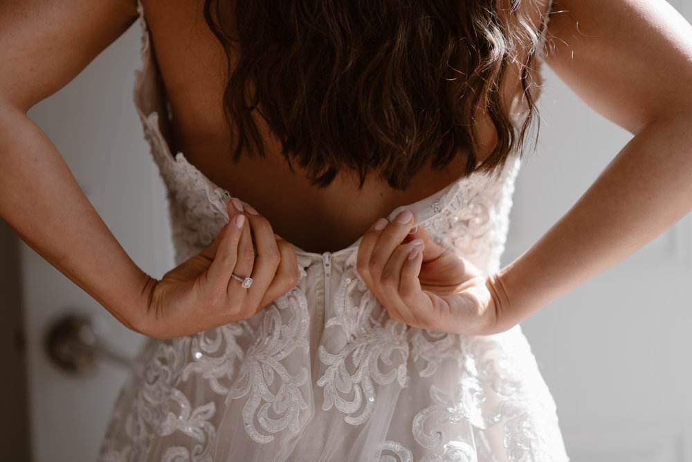 A close-up view, shot by elopement wedding photographer Adventure Instead, of the bride zipping up the back of her wedding dress in her Alaska airbnb before her destination elopement.