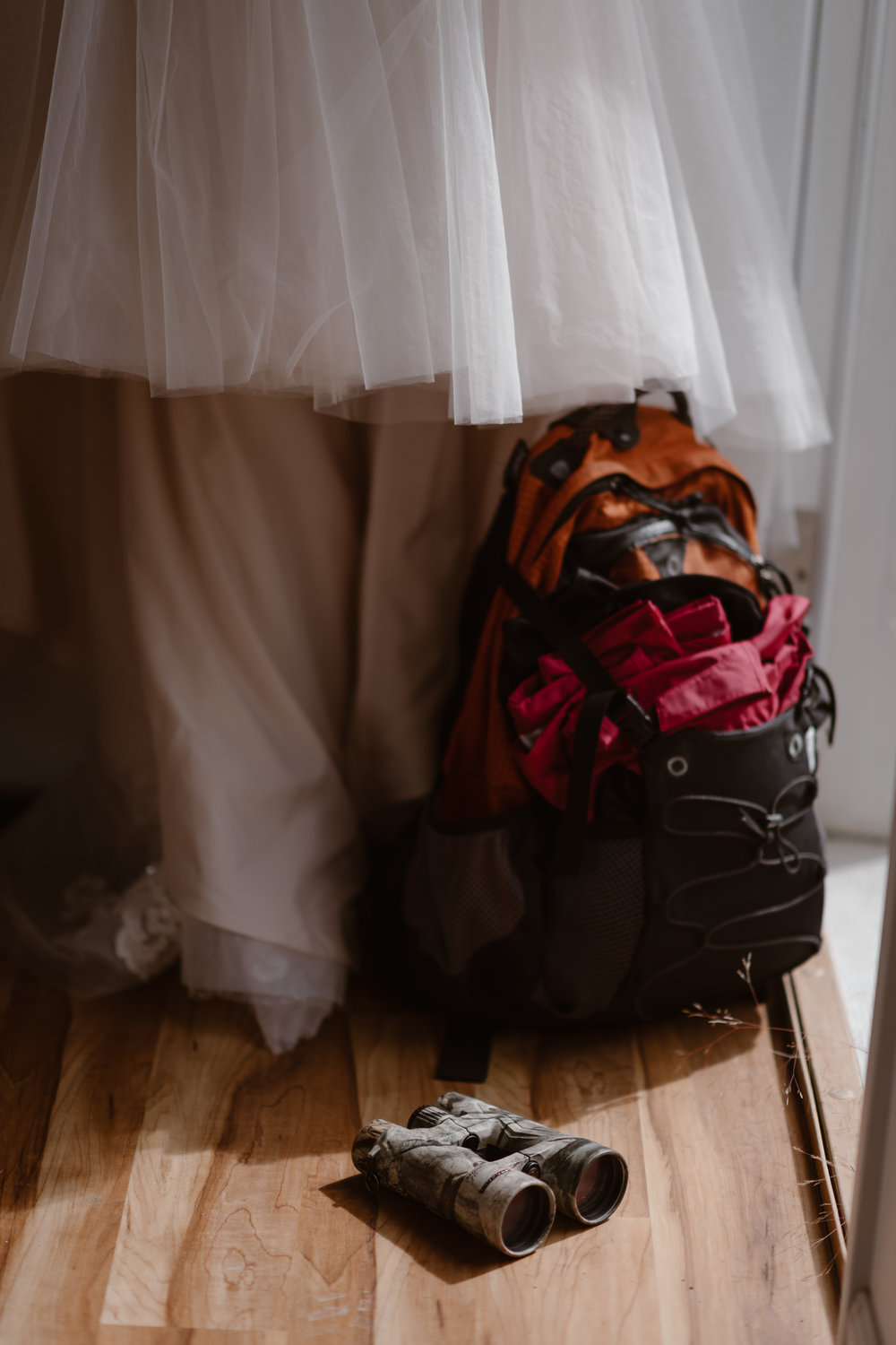 Beneath the skirt of a wedding dress sits a backpack and a pair of dirt-covered binoculars, all items that will be used in this couple's alaska elopement. This image was captured by Adventure Instead, adventure photographers who help couples create unique eloping ideas.