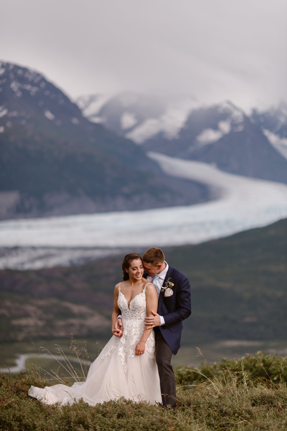 Jordyn and Connor snuggle and embrace in their wedding attire as they stand on the green, lush side of a mountain. In the background of this elopement photo is a glacial lake and glaciated peaks — two gorgeous features the couple wanted to see during their Alaska helicopter elopement story.