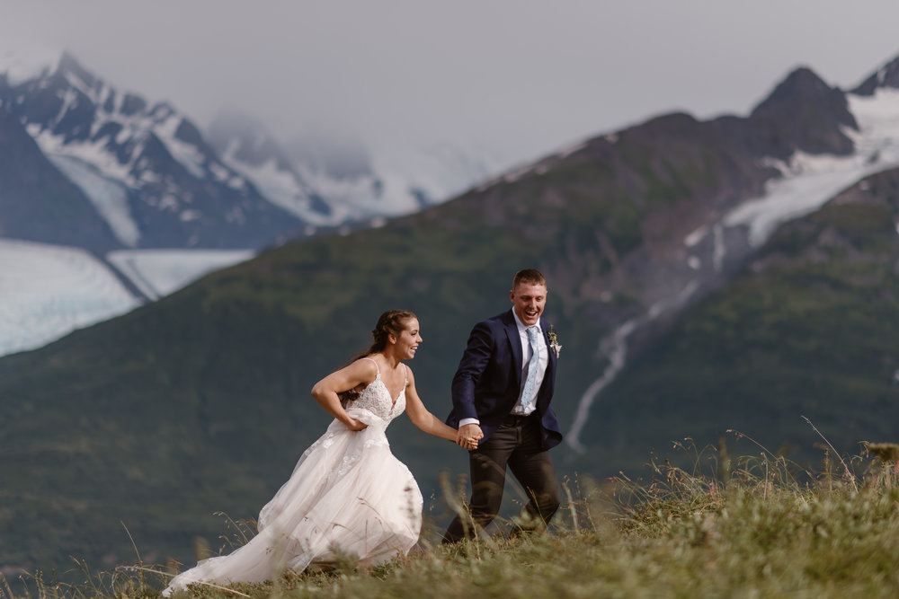 The bride and groom take hands and run in a green meadow with a glaciated-peak in the background. Jordyn and Connor helicoptered into this Alaska location for their destination elopement, captured by Adventure Instead, Alaska wedding photographers.