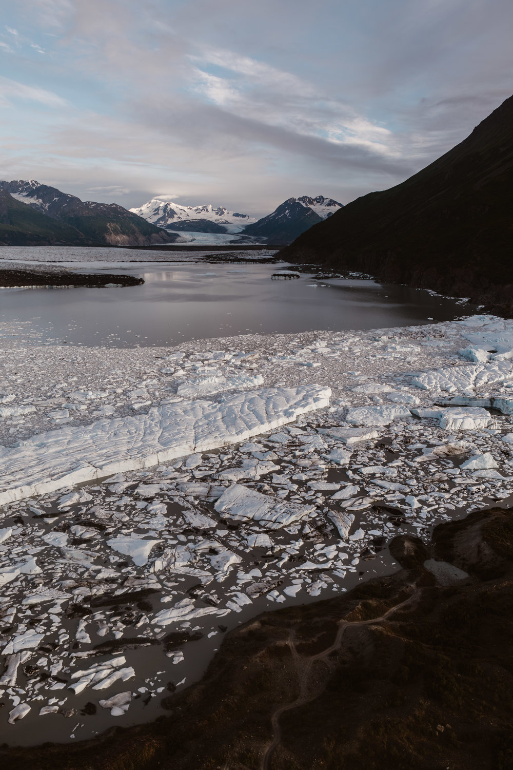 This photo shows views of an Alaska glacial landscape, including a rocky beach, a glacial lake with enormous chunks of ice floating in it, and snowy mountains peaks in the backdrop. All of this can be seen from a birds-eye-view of from the helicopter carrying the bride and groom to their destination elopement spots.