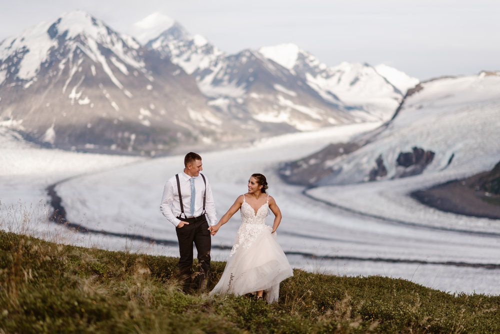 Jordyn and Connor hold hands as they walk away from a gorgeous scene behind them — a glacial lake and a handful of snowy mountain peaks. This elopement photo was captured by Adventure Instead, Alaska wedding photoraphers.