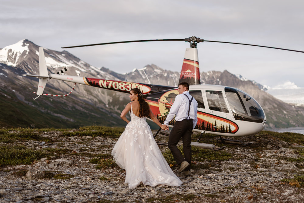 The bride and groom head toward the helicopter, which has landed to take them to another destination elopement spot. Jordyn and Connor have their backs to the camera, facing a dramatic landscape of icy mountain peaks.