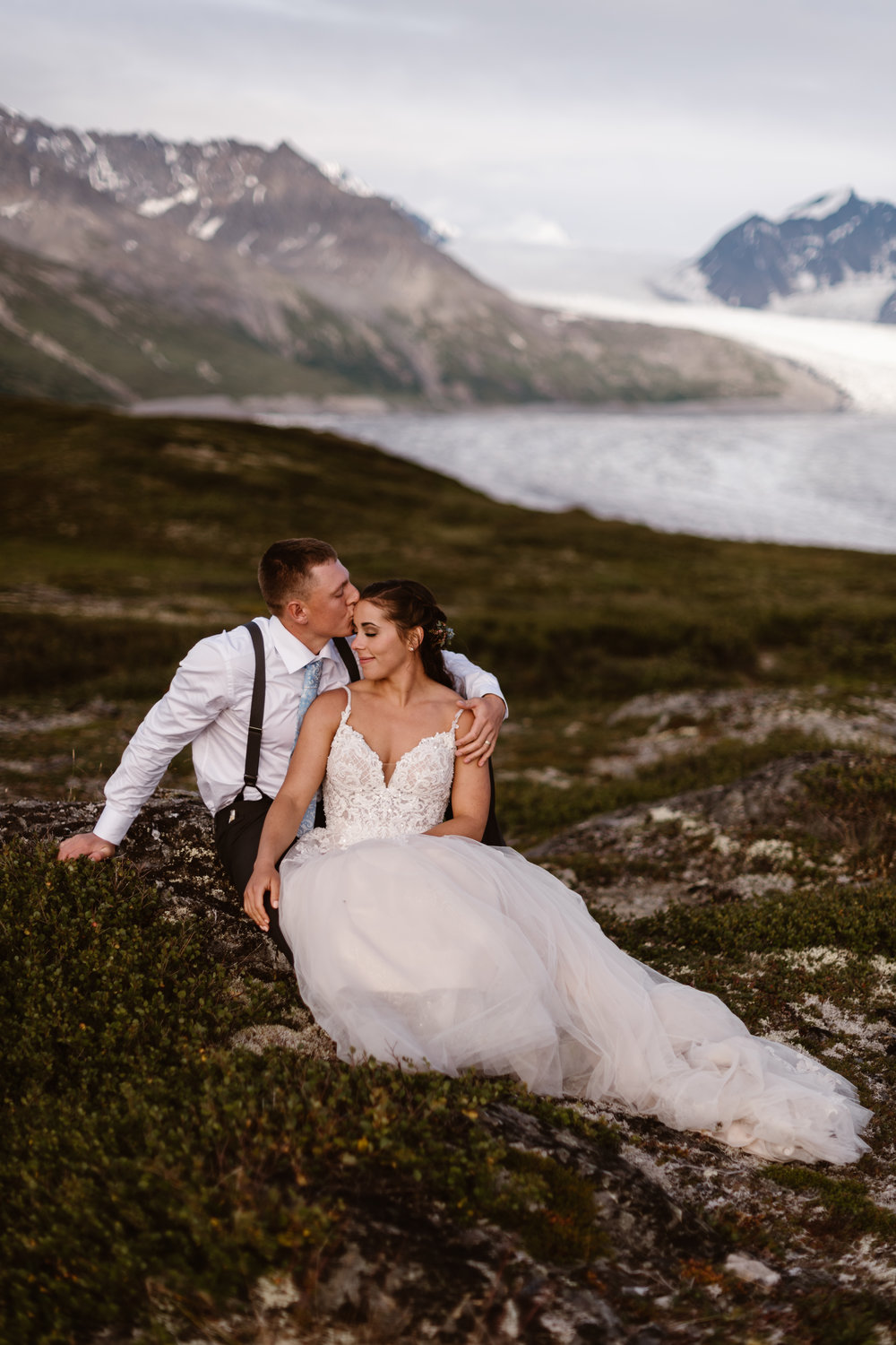 The bride and groom sit down on the lush, green mountainside. Connor, the groom, wraps his around Jordyn and kisses her forehead in these elopement photos taken by Adventure Instead, an elopement wedding photographer. Jordyn leans into Conner with her eyes closed as they sit among glacial peaks and a glacial lake.