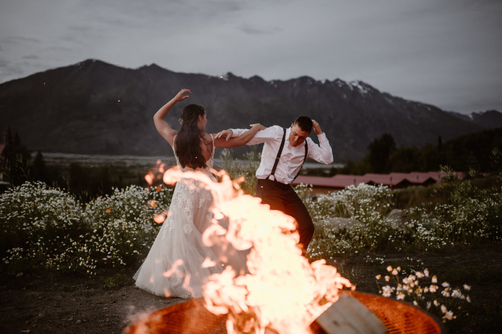 Jordyn and Connor bust out some special dance moves for their first dance in front of a roaring campfire during blue hour. As sparks fly from the campfire, the two twist around and show off their skills with a giant mountain jutting toward the sky behind them.