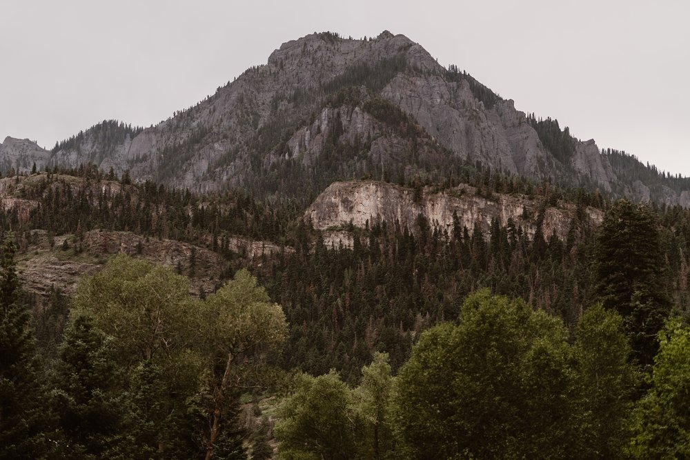 An enormous granite mountain peeks out behind younger, tree-covered mountains. Every shade of evergreens dot the granite mountain. These are gorgeous features couples can expect when they plan a Colorado mountain wedding.