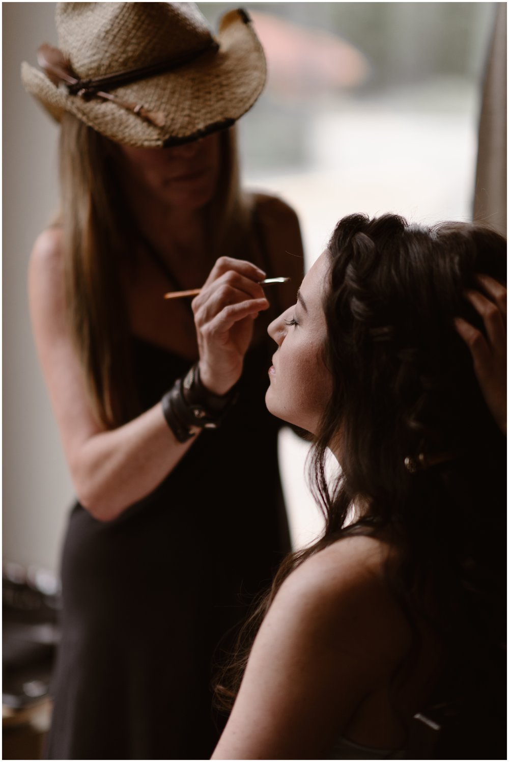 A makeup artist in a cowboy hat leans in to apply makeup to the bride, Katie. With her eyes closed, Katie patiently allows the makeup artist to do her job to get her ready for her Colorado mountain wedding. These adventure photos were captured by Adventure Instead, an adventure wedding photographer.