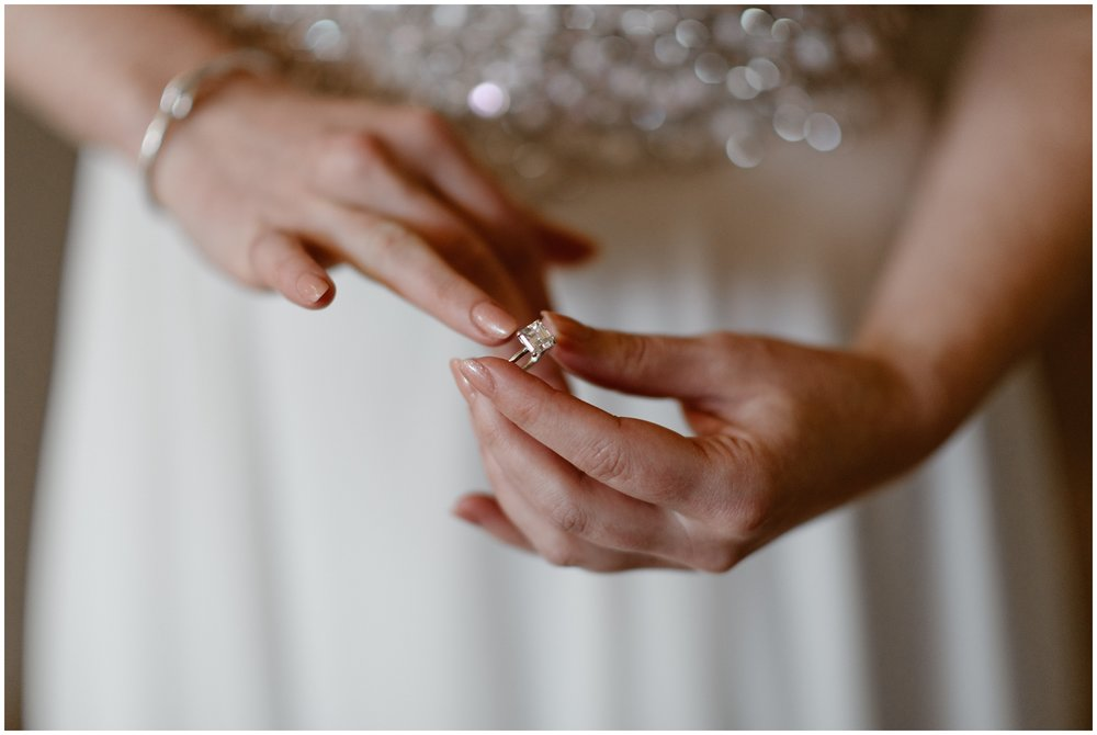 Katie, the bride, places her engagement ring on her finger. Blurred in the background, her pearl-decorated wedding dress glimmers in the light. This unique eloping idea was captured by Adventure Instead, an adventure wedding photographer.