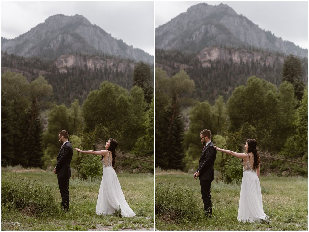 These side-by-side elopement pictures show-off Katie and Logan's (the bride and groom's) first look moment in Ouray, Colorado. In the background, an enormous moutnain peak can be seen, with dozens of green trees peeking out. In the elopement photo on the left, Katie reaches out, just a few inches away from Logan's shoulder. Logan is turned in the opposite direction. In the picture on the right, Katie touches Logan's shoulder before their off-road 4x4 wedding.