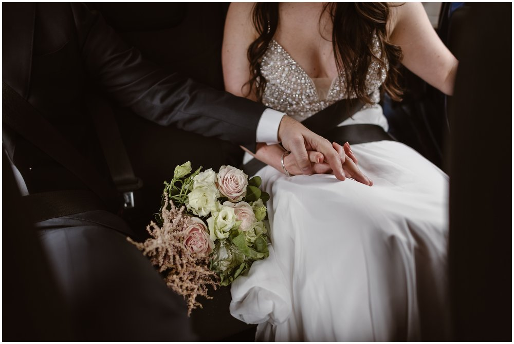 A close-up elopement picture shows a photo of Katie and Logan, a bride and a groom, holding hands in the backseat of their Jeep wedding car. A bouquet of flowers sits between the two as they get ready to take off for their Colorado elopement.
