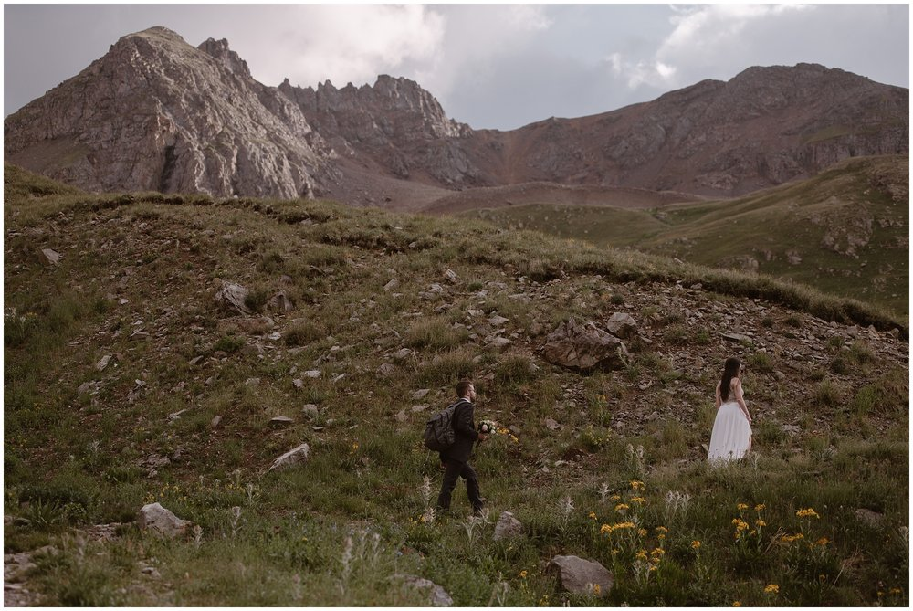 Logan, the groom, follows Katie, the bride, up a trail that cuts through a lush, green meadow. In the field, yellow and white wildflowers bloom, surrounded by chunks of granite rocks. In the background of this Colorado elopement photo, enormous red and granite mountains are seen.