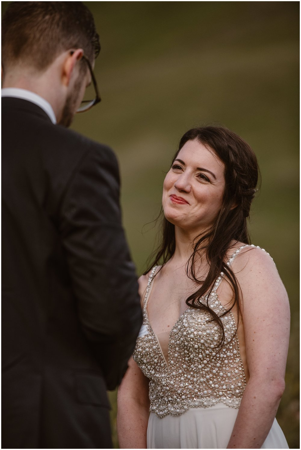 The camera zooms in on Katie, the bride, staring at her groom reading his vows to her. Katie is in a white and pearl-beaded wedding dress for her elopement ceremony as part of her 4x4 wedding.