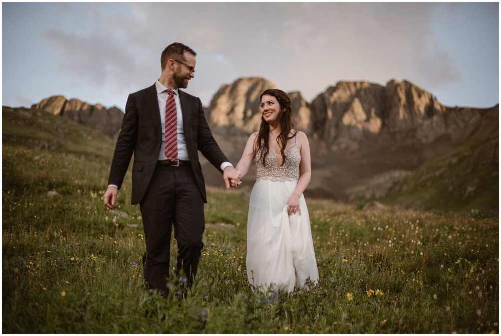 The bride and groom take hands as they walk through a meadow at the base of a mountain. in the background, a golden light is cast on the rocky mountain face. Katie an Logan, the bride and groom, chose this spot for their elopement ceremony for their Colorado mountain wedding, which was captured by Adventure Instead, an elopement wedding photographer.