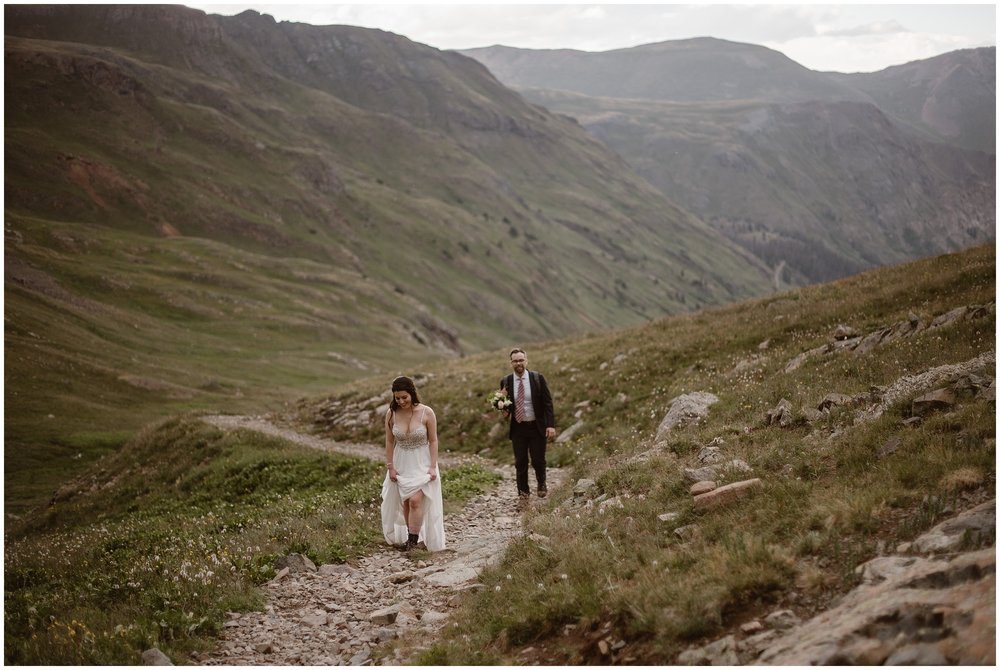 Katie and Logan, the bride and groom, walk down a rocky pathway from where they just had their elopement ceremony for their Colorado mountain wedding, back toward the Jeep wedding car that will take them back down to Ouray. These adventure elopement pictures were captured by elopement wedding photographer Adventure Instead.