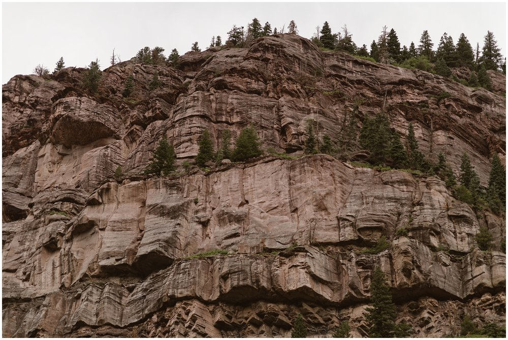 The sand-colored side of a mountain juts out from a rocky mountain face in this photo. This brown, taupe, a gray mountain side is a young mountain in the heart of Ouray, Colorado, a popular spot for couples who want an adventure elopement.