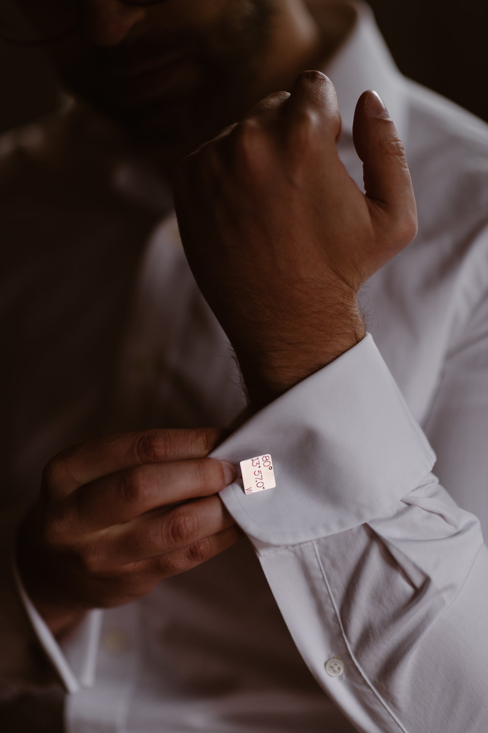 The groom, Logan, adjust the long, white sleeve of his shirt, showing off his cuff links that are engraved with a specific longitude and latitude. This unique eloping idea was a meaningful part of this couple's jeep Colorado elopement.
