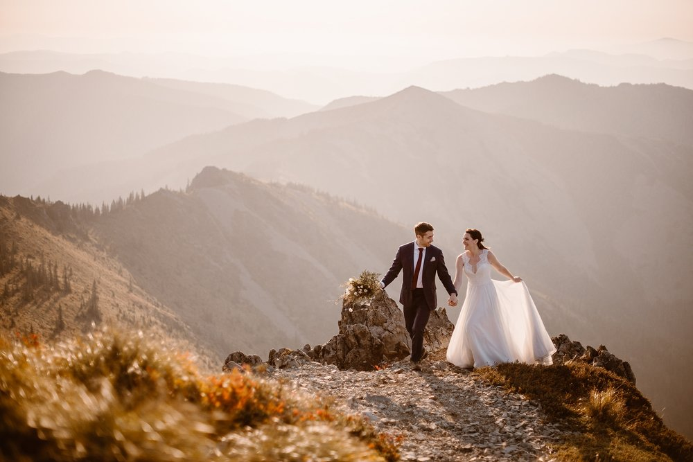 A bride and groom take hands on the side of a mountain and bask in the golden, glowing light the sun is casting of them. Off in the distance of this elopement photo, several mountain ranges can be seen.