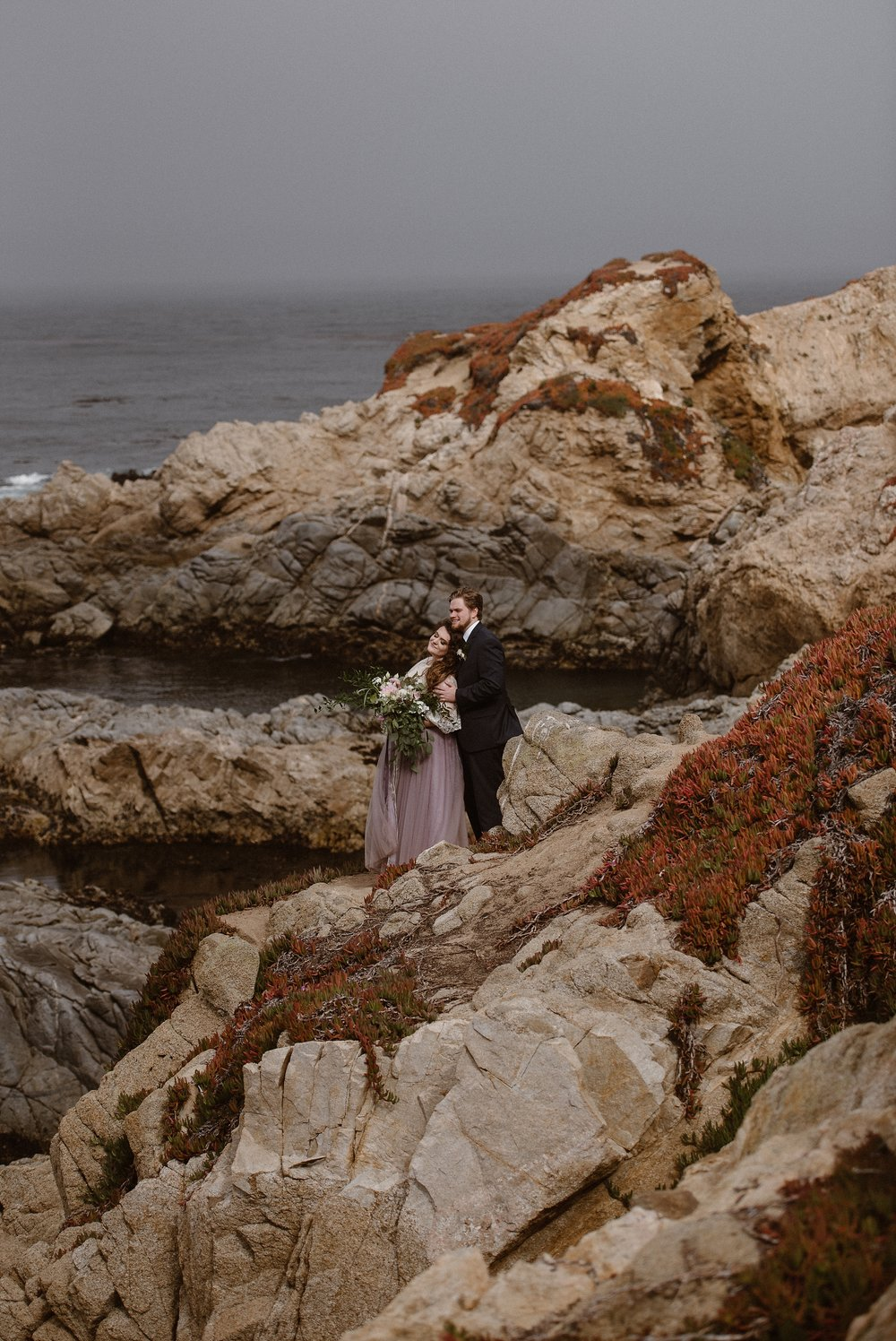 A bride, wearing a soft, purple gown, leans against her groom, in a black suit, as they stand among the rocky crags along the Washington Coast. In the distance, the Pacific Ocean is calmly lapping up against the rocks. Tiny bursts of red flowers are blooming on the side of these coastal rocks.