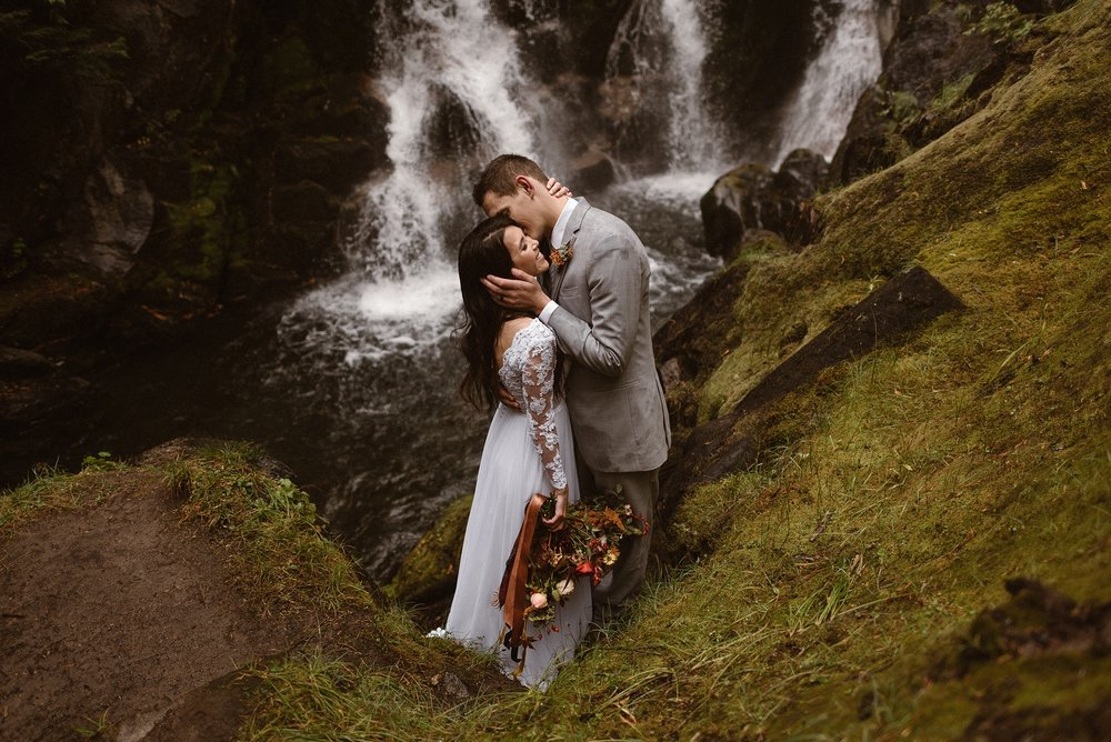 A newly married couple embrace as they stand on a mossy, lush piece of land next to a cascading waterfall in a Washington forest. This elopement picture was captured by Washington elopement photographer Adventure Instead.